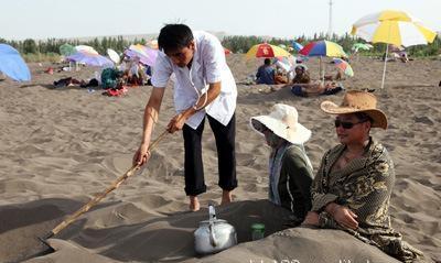 沙疗场地的工作人员帮助顾客埋沙