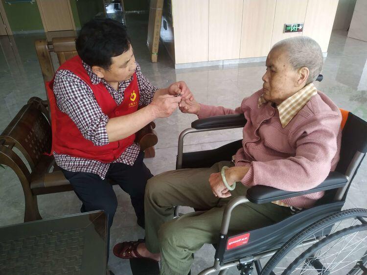 养老院工作人员专心为老奶奶剪指甲!